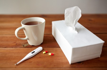 Tissue, cup of tea, and thermometer
